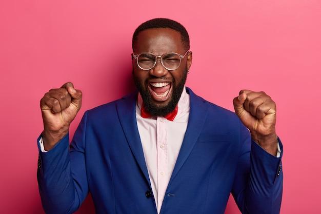 Poderoso homem negro alegre grita e ergue os punhos cerrados, triunfa do sucesso, mantém a boca aberta, usa roupas elegantes e formais