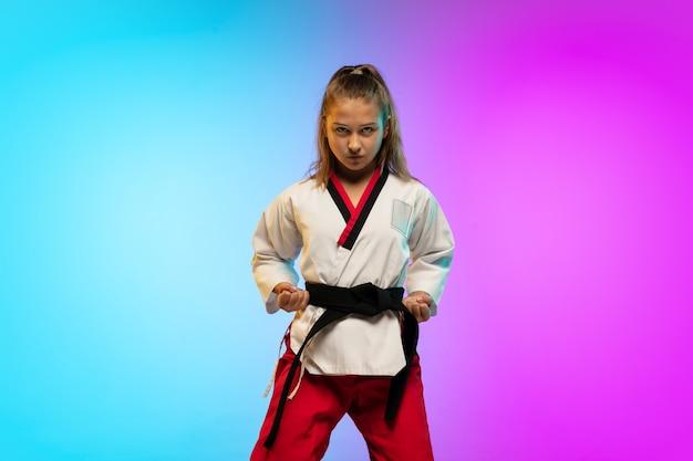 Poderoso. karatê, garota de taekwondo com faixa preta isolada em fundo gradiente em luz de néon. pequeno modelo caucasiano, garoto do esporte, treinamento em movimento e ação. esporte, movimento, conceito de infância.