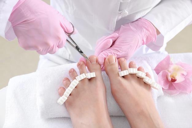 Podiatra cortando pele dura de pés de jovem em salão de spa