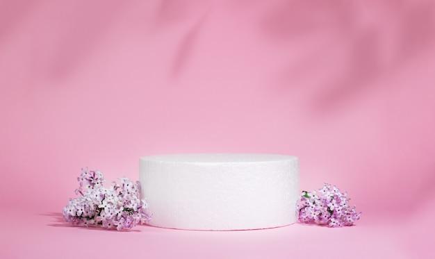 Pódio cilíndrico branco sobre um fundo rosa com sombras duras e flores lilás. cena mínima de apresentação de produto cosmético vazio. pódio geométrico.