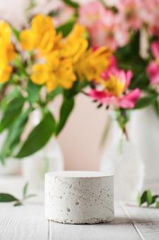 Pódio de concreto vazio para a apresentação de seu produto com flores no fundo em um clima de primavera