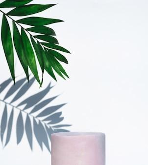 Pódio de frasco cosmético e folha verde com sombra no fundo branco