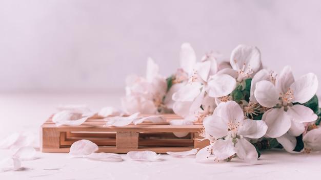 Pódio de madeira em forma de palete sobre superfície de gesso leve com flores de maçã. pódio, pedestal ou palco. maquete para produtos cosméticos. bandeira