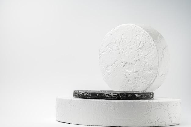 Pódio de pedestal redondo branco e preto. pedestal de cimento abstrato por holofotes em fundo branco