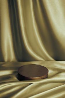 Pódio ou pedestal vazio para perfume ou produto cosmético em tecido de cetim dourado com dobras