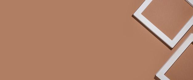 Pódio para quadros quadrados brancos de apresentação em fundo marrom. vista superior, configuração plana. bandeira.