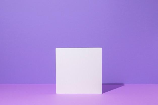 Pódio quadrado branco para apresentações de pedestal em um fundo lilás.