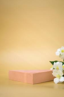 Pódio triangular para demonstração de cosméticos, produtos em fundo bege e jasmim