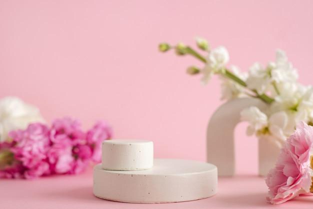 Pódio vazio para apresentação de produtos cosméticos. flores em tons pastel na vista lateral de fundo rosa