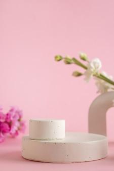 Pódio vazio para apresentação de produtos cosméticos. flores pastel em fundo rosa vista lateral vertical