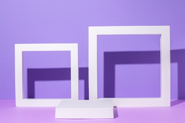Pódios quadrados de branco e moldura para apresentações de pedestal em um fundo lilás.