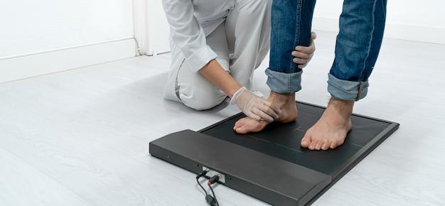 Podólogo irreconhecível examinando os pés dos pacientes