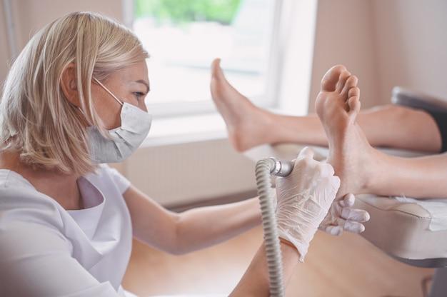 Podólogo usando equipamento de retificação e polimento de procedimento para pedicure de pés