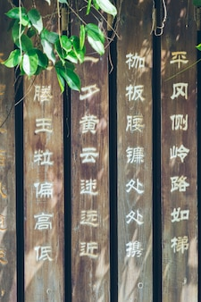 Poemas antigos chineses esculpidos nas tábuas do parque, plantas verdes