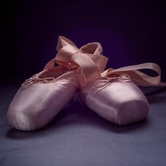 Pointe calça as sapatas da dança de bailado com uma curva das fitas dobradas belamente em um fundo escuro.