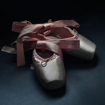 Pointe sapatos sapatos de dança de balé com um laço de fitas lindamente dobrado no escuro