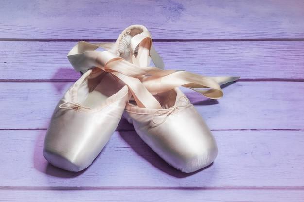 Pointe sapatos sapatos de dança de balé com um laço de fitas maravilhosamente dobrado na madeira