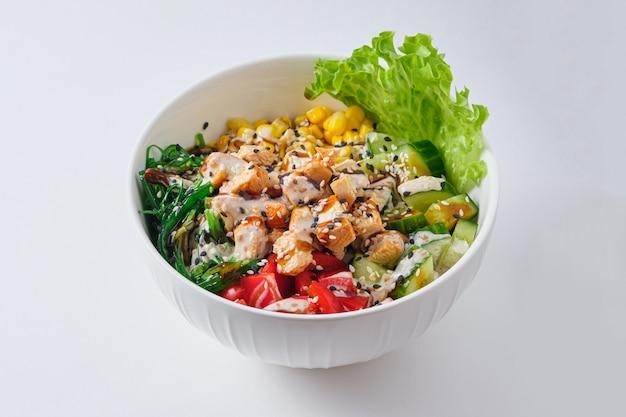 Poke bowl com frango, milho, pimenta, arroz e chukoy. prato em um prato branco.