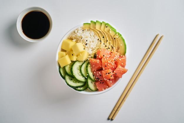 Poke bowl com salmão, abacate, manga, isolado com pauzinhos de molho de soja
