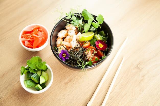Poke salada com camarão em uma tigela. ingredientes camarão, espinafre escaldado, tomate cereja, arroz, pepino, molho de soja e gengibre, molho picante, nori, gergelim, limão, coentro. conceito de salada de frutos do mar asiáticos.