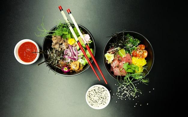 Poke saladas com atum e carne em tigelas sobre a mesa duas tigelas de poke salada com pauzinhos em um gr ...