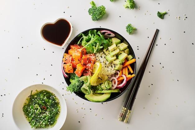 Poke tigela com salmão, abacate pepino pauzinhos e molho de soja