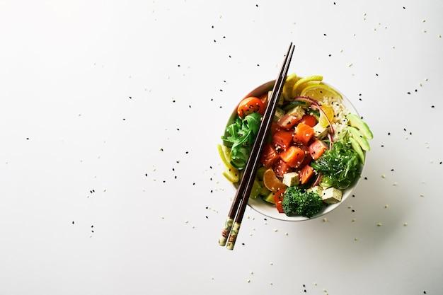 Poke tigela com salmão, abacate, pepino, rúcula, brócolis, cenoura com chuka salada, pauzinhos