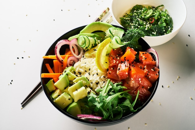 Poke tigela com salmão, abacate, pepino, rúcula, brócolis, cenoura de arroz com pauzinhos de salada chuka