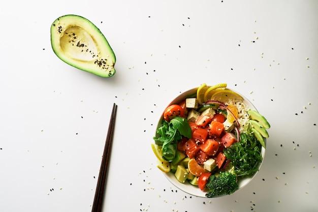 Poke tigela com salmão, abacate, pepino, rúcula, brócolis, pauzinhos