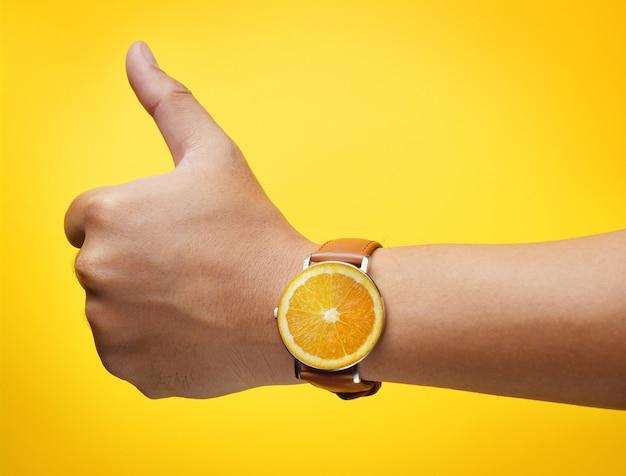 Polegar mão vestindo fruta laranja relógio em fundo amarelo