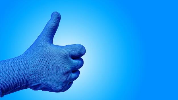 Polegar o gesto com a mão na luva isolada em fundo azul
