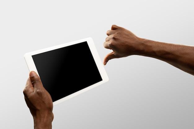 Polegar para baixo, não gosto. feche as mãos masculinas segurando um smartphone com tela em branco durante a exibição online de jogos de esporte popular, campeonatos. copyspace para anúncio. dispositivos, gadgets, conceito de tecnologias.