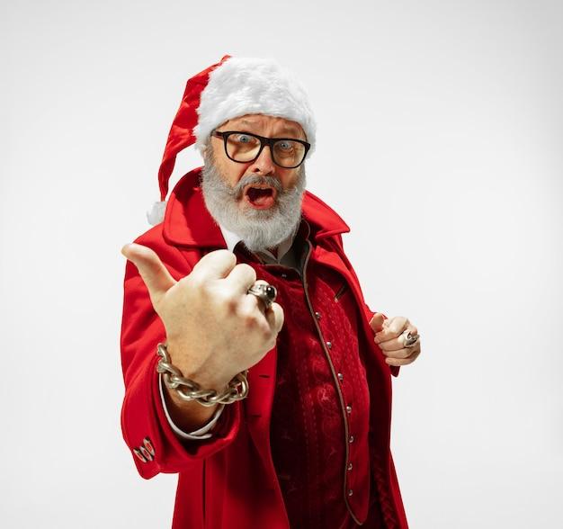Polegar para cima, legal. moderno e elegante papai noel em elegante terno vermelho, isolado no fundo branco. parece uma estrela do rock. reveillon e natal, comemoração, feriados, clima de inverno, moda.