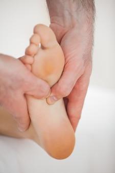 Polegares de um médico massageando um pé