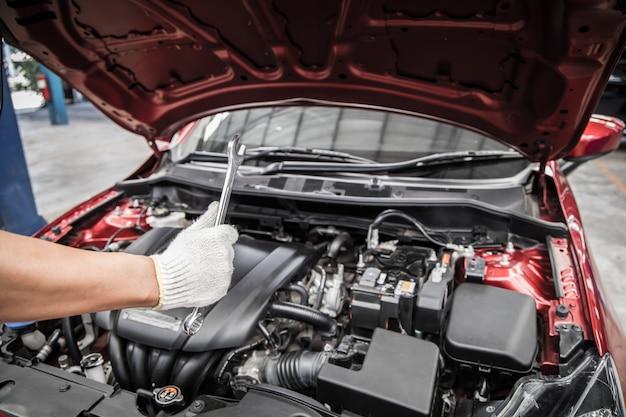 Polegares para cima e segurando a chave do mecânico de automóveis, fazendo manutenção e serviço de carro.