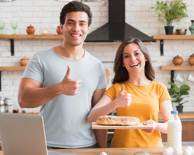 Polegares para cima gesto casal cozinhar um pão