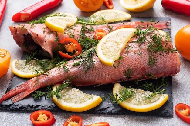 Poleiro de peixe cru com rodelas de limão e endro, pimenta.