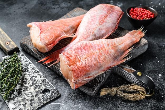 Poleiro vermelho cru ou peixe robalo em uma placa de corte. vista do topo.