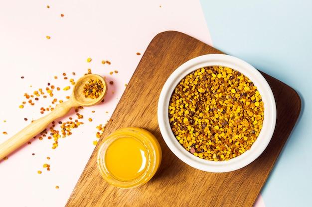 Pólen de abelha e pote de mel na tábua de madeira sobre o pano de fundo branco