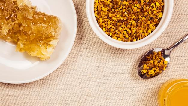 Pólen de abelha; favo de mel; mel, arranjado em fundo de juta