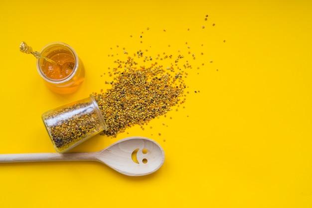 Pólenes de abelha derramados; pote de mel e sorridente colher de pau em pano de fundo amarelo