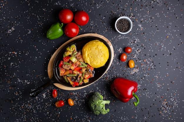 Polenta com guisado, em preto, com tomate, pimentão vermelho e brócolis