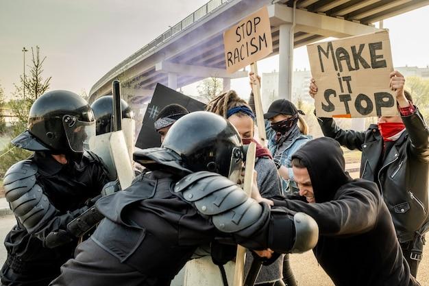 Polícia de choque com capacetes empurrando os manifestantes com escudos enquanto lutava contra eles no comício