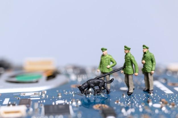 Polícia e detetive em miniatura estão trabalhando em uma placa-mãe de computador, conceito de crimes cibernéticos