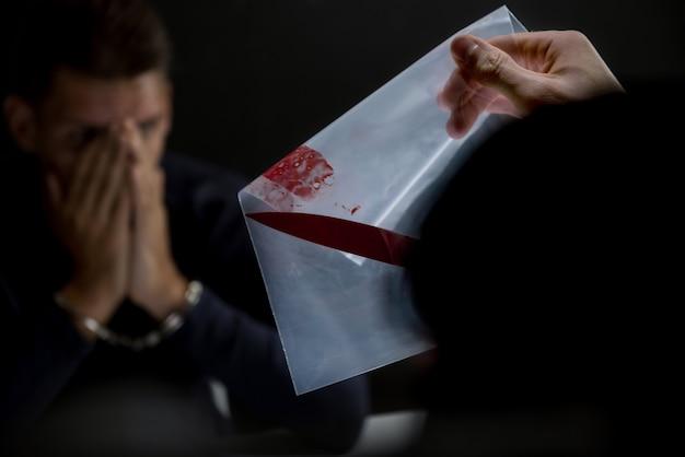Polícia na sala de interrogatório mostrando uma faca com sangue como prova de assassinato