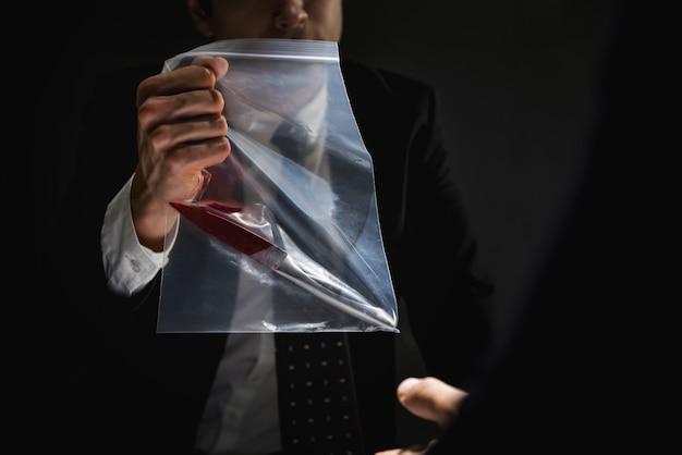 Polícia na sala de interrogatório mostrando uma faca como prova de assassinato