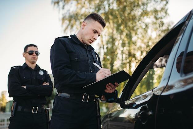 Policiais do sexo masculino verificam veículo na estrada