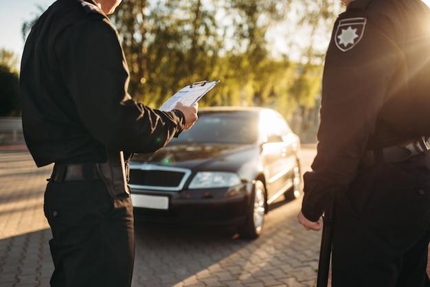 Policiais uniformizados param o carro na estrada