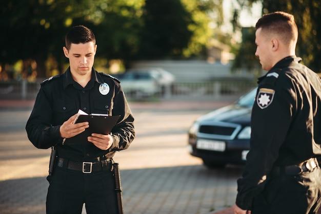 Policiais uniformizados verificam o carro na estrada