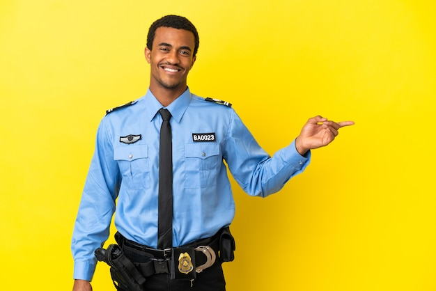Policial afro-americano sobre fundo amarelo isolado apontando o dedo para o lado